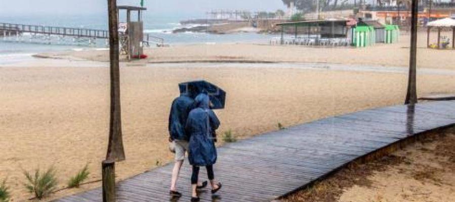 Dos personas se protegen de la lluvia, mientras pasean por la playa de Camp de Mar, en Mallorca.