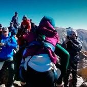 Unos montañeros ayudan a una mujer con discapacidad a alcanzar la cima de una montaña