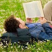 Un chico leyendo en un parque