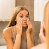 Mujer se mira el rostro en el espejo