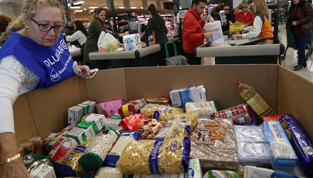 Una voluntaria del Banco de Alimentos colocando los alimentos donados por los clientes de un supermercado