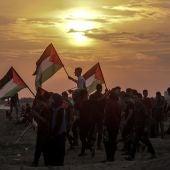 Varios palestinos ondean sus banderas durante enfrentamientos con soldados israelíes en la Franja de Gaza