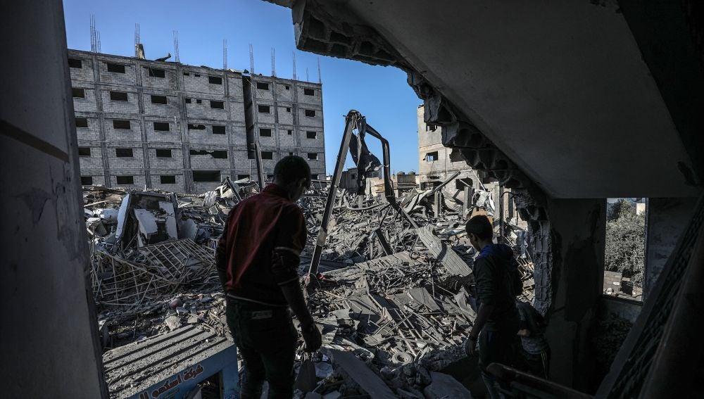 Un par de palestinos caminan entre los escombros en Gaza