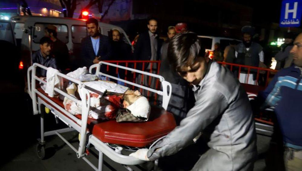 Miembros de los servicios de emergencia transportan en camilla a un herido tras un ataque suicida en Kabul, Afganistán