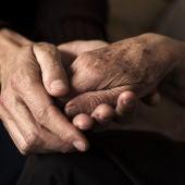 Las manos de dos personas mayores