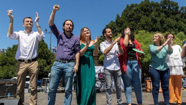El secretario general de Podemos, Pablo Iglesias, junto a otros candidatos saludan a los asistentes al acto electoral que celebran en Sevilla