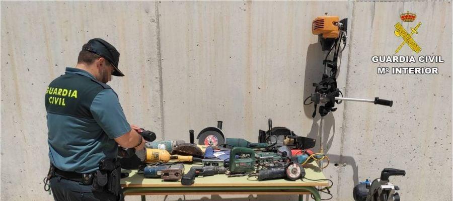 Agente d ela Guardia Civil junto a efectos recueprados en la operación policial.