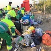Trabajadores de Urbaser recogen basura en una playa de Elche tras la noche de San Juan de 2019.