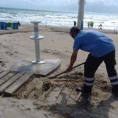 Un operario de Urbaser repara una pasarela en la playa de Arenales del Sol.