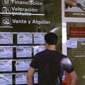 Un hombre mira las viviendas en venta en una inmobiliaria