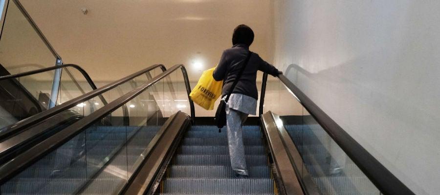 Una mujer sube en unas escaleras mecánicas