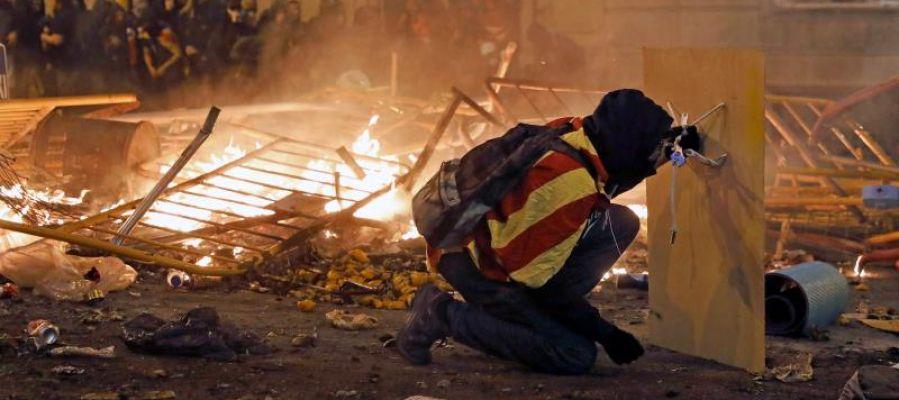 Un manifestante se protege con una plancha de madera durante los disturbios en Barcelona