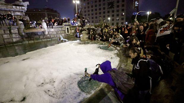 Centenares de personas convocadas por los CDR tiran 'Fairy' a la fuente de la plaza España de Barcelona