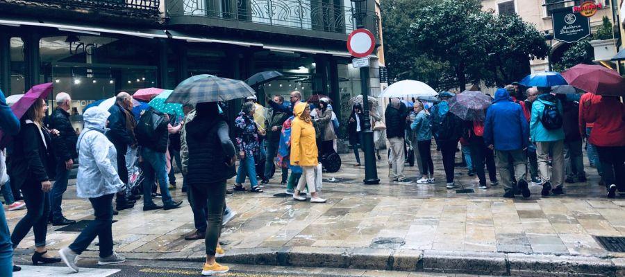 Ciudadanos paseando bajo la lluvia en el centro de Palma.