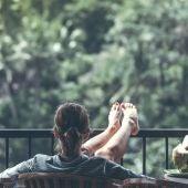 Una mujer apoya los pies en una barandilla