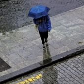 Una persona camina con un paraguas por la lluvia.