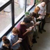 Un grupo de jóvenes usando su móvil