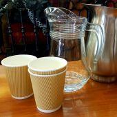 Jarras de cristal y metal junto a vasos de plástico.