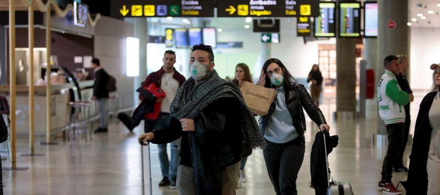 Coronavirus | Gente con mascarillas en el Aeropuerto de Manises (Valencia)