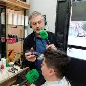 Carlos Alsina cortando el pelo al peluquero que rapó al grupo de niños solidarios con su amigo