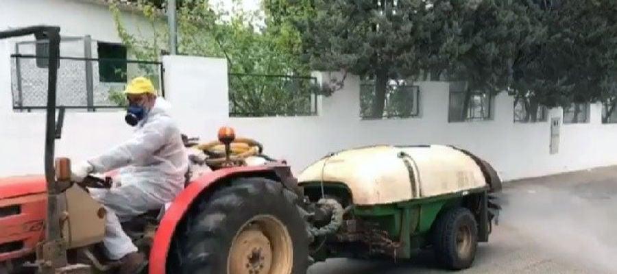 Tractor con cisterna y atomizador desinfectando las calles de una localidad.