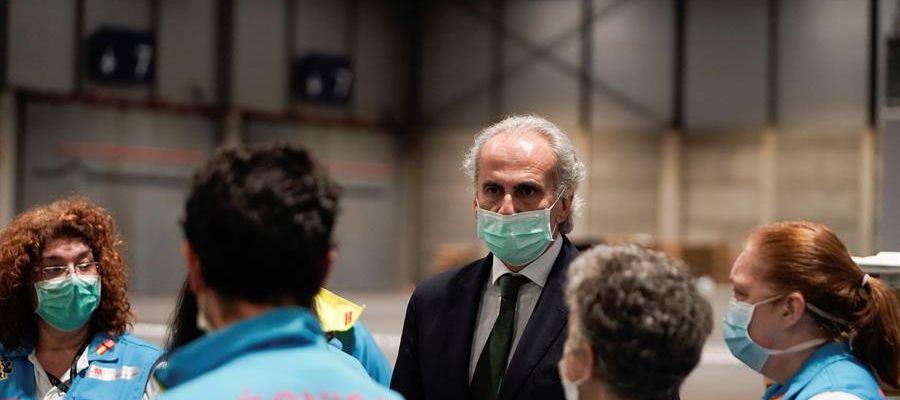 Enrique Ruiz Escudero, conversa con personal sanitario que prepara camas en uno de los pabellones del recinto ferial Ifema