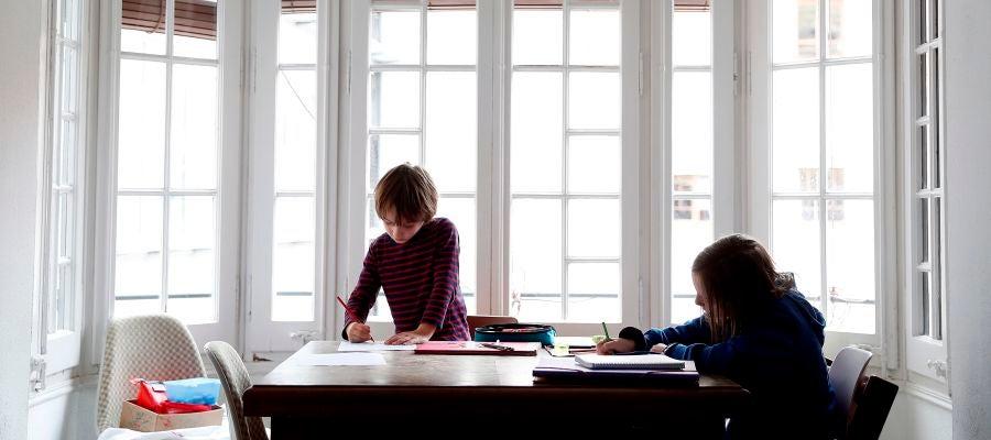Dos niños hacen sus deberes en su casa
