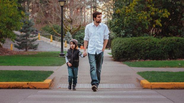 Un padre camina por la calle con su hijo