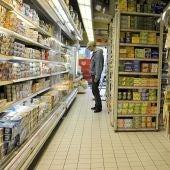 Un cliente observando las estanterías de un supermercado