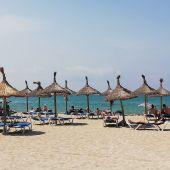Turistas en hamacas bajo las sombrillas de la Playa.