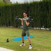 Juanmi, jugador del Betis, levanta pesas en su domicilio.