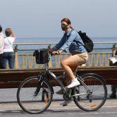 Una mujer pasea en bicicleta protegida con una mascarilla