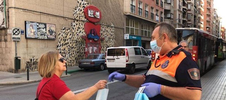 Un voluntario de Protección Civil entrega una mascarilla a una mujer en Elche.