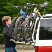 Un hombre carga unas bicicletas en su vehículo