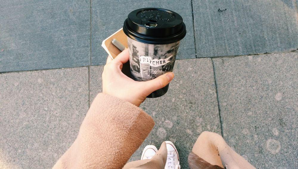 Una mujer con un café para llevar