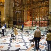 Fieles en el Altar Mayor de la Catedral de Sevilla