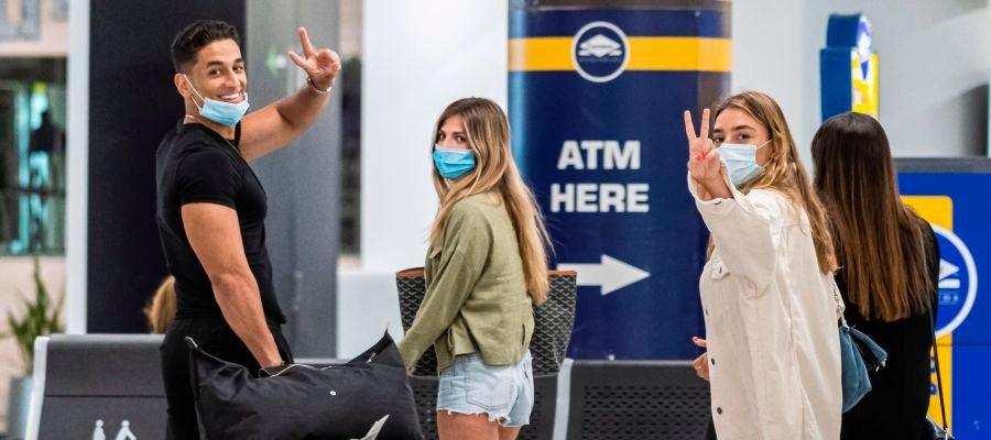 Viajeros ataviados con mascarillas
