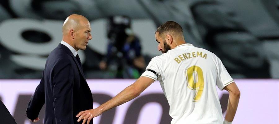 Zidane y Benzema charlan en la banda durante un partido del Real Madrid.