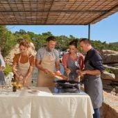Pla general d'un grup de persones fent un tast de vins i cuinant un plat durant una excursió enogastronòmica pels camins de ronda de la Costa Brava