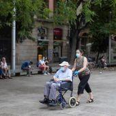 Dos personas pasean con mascarilla