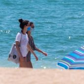 Dos jóvenes con mascarilla en una playa de Andalucía