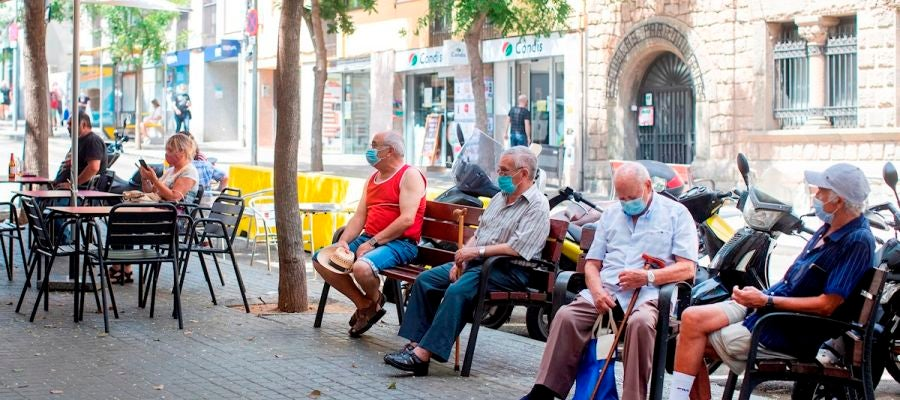 Gente con mascarillas en una calle del barrio de El Carmel de Barcelona