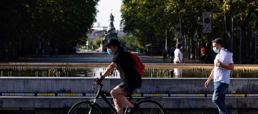 Un hombre circula en bicicleta y con mascarilla por el centro de la ciudad de Valladolid