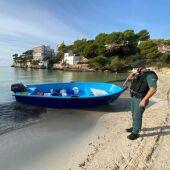 Un agente de la Guardia Civil contempla una patera llegada a Mallorca.