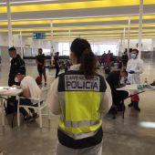 Agentes de la Policía Nacional atienden a migrantes llegados a las costas de Baleares.
