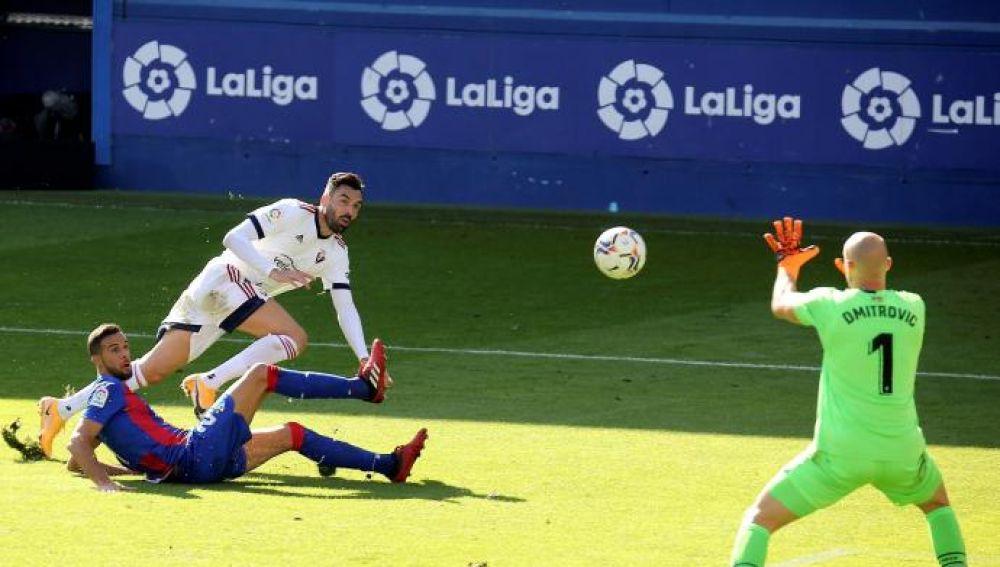 El delantero del Osasuna Enric Gallego (c) remata ante el jugador de la SD Eibar Burgos, y el guardameta Dimitrovic
