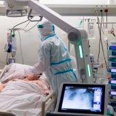 Un sanitario hace una radiografía del pecho a un paciente ingresado en la UCI por COVID-19.