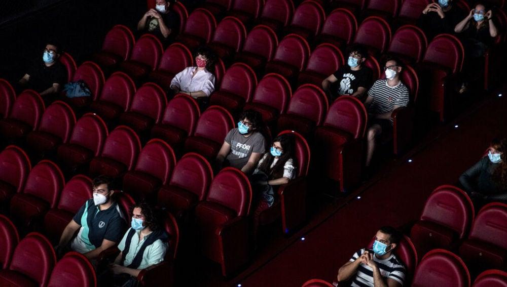 Espectadores en una sala de cine, distanciados y con mascarilla