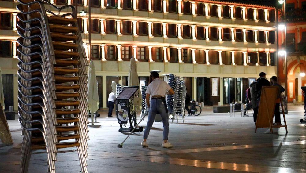 Un camarero recogiendo la terraza de su bar en Córdoba el domingo