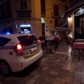 Un coche de la policía Local pasa por la puerta de un restaurante en Málaga